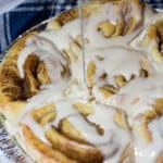 Cinnamon rolls in a baking pan topped with vanilla icing.