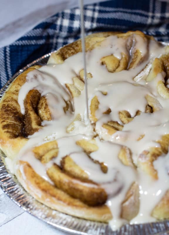 Vanilla icing being drizzled onto a pan of homemade cinnamon rolls.