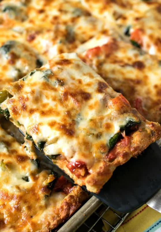 Sheet pan pizza cut into slices, topped with cheese and vegetables.