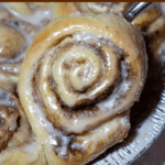 Close up of cinnamon roll being pulled from a tin pan.