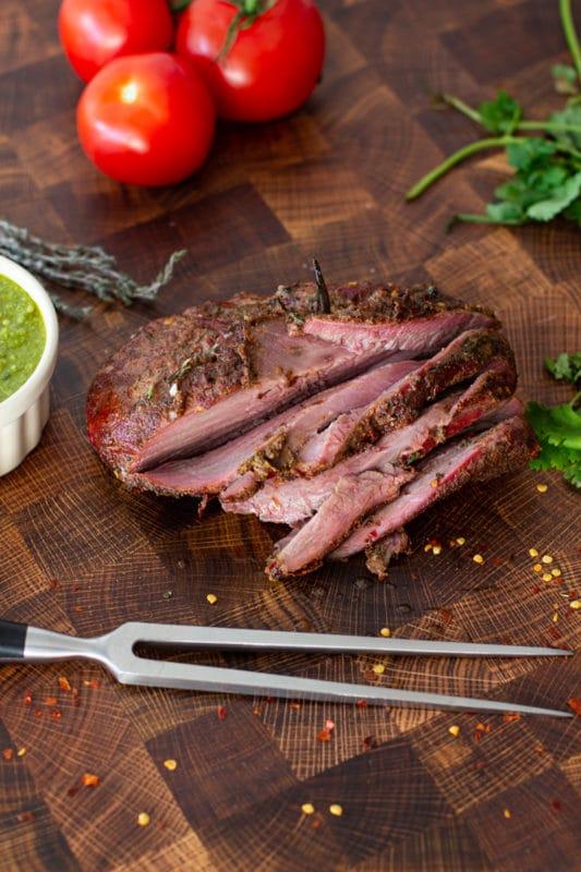 Sliced roast on a cutting board, parsley on table.