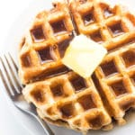 Waffles on a plate topped with butter and syrup, fork on table.