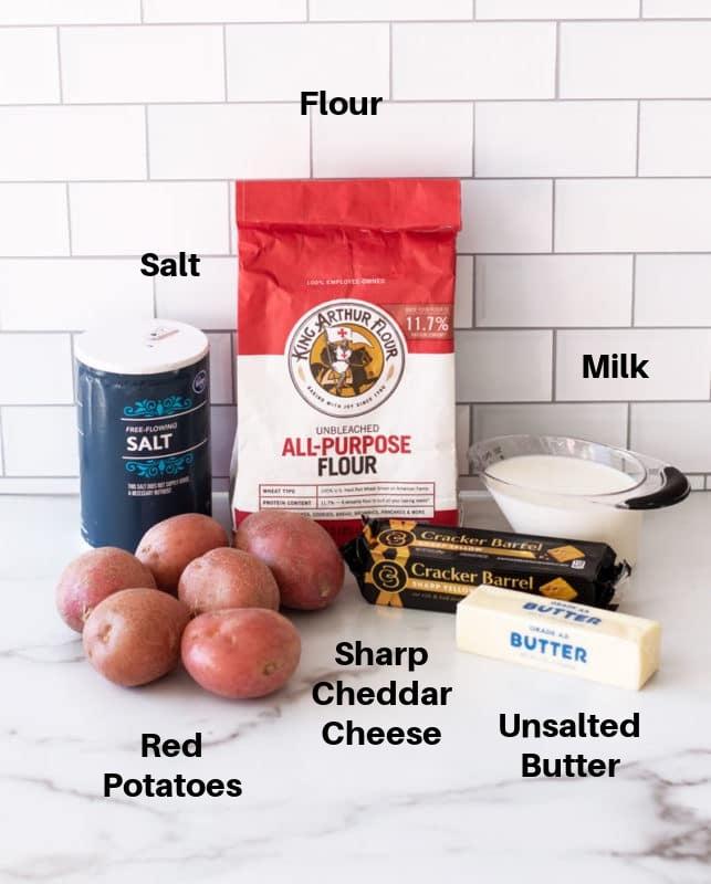 Red potatoes, flour, milk, sharp cheese, butter, salt on counter to make potato soup.