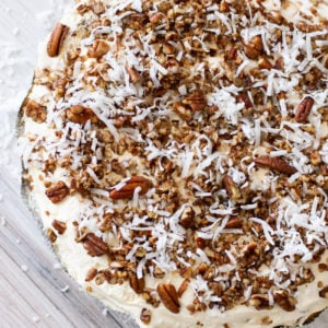 Frozen caramel pie on counter top topped with pecans and coconut.