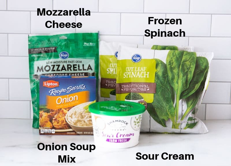 Bags of frozen spinach, sour cream, onion soup mix and mozzarella cheese on a counter.
