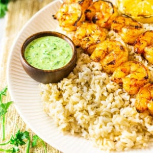Plate containing rice and grilled shrimp.