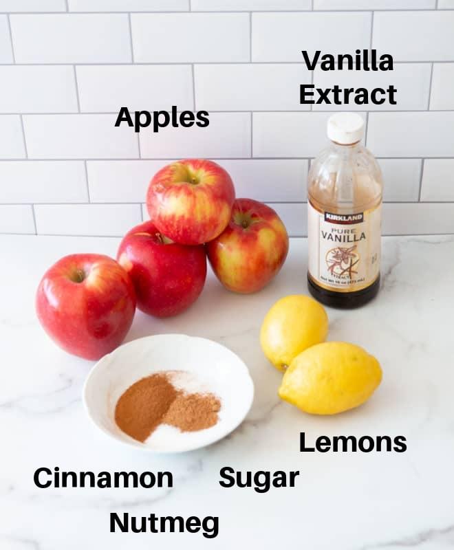 Four gala apples, vanilla extract, lemons, nutmeg, cinnamon, and sugar on a counter.