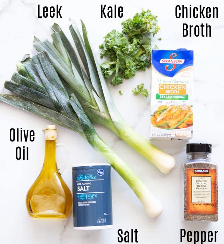 Leek, kale, chicken broth, olive oil, salt and pepper on table.