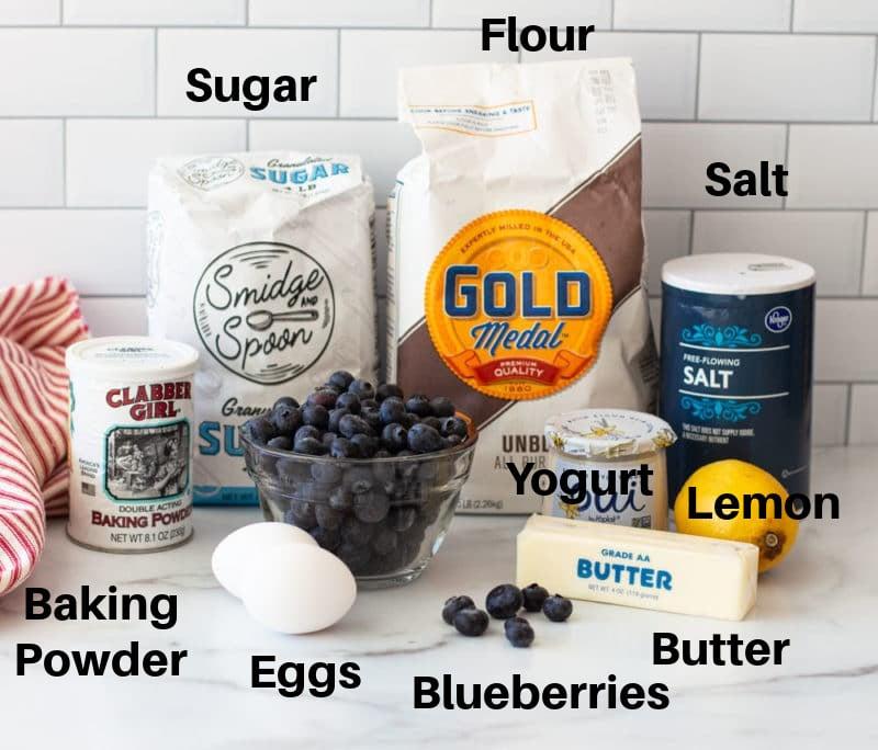 Flour, blueberries, yogurt, butter, eggs, saltt, lemon, baking powder on a counter.