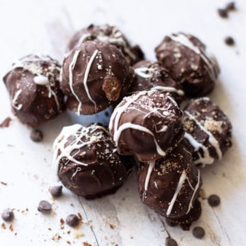 8 chocolate truffle amaretto balls on a counter, chocolate chips on table.
