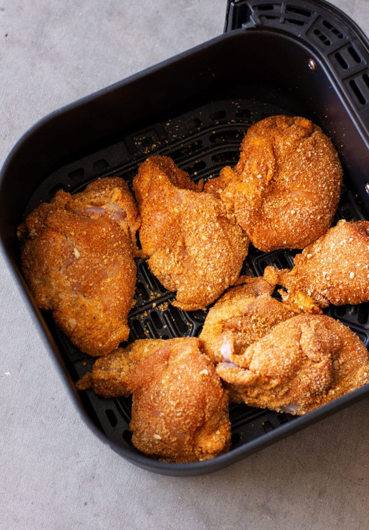 Air Fryer Pan containing breaded chicken thighs.