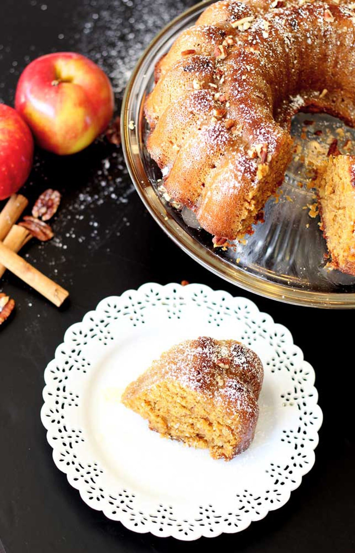 Sliced apple pumpkin bundt cake sitting on a glass cake platter, white lace plate containing a slice of cake with 2 red apples with cinnamon stick and pecans on a black table.