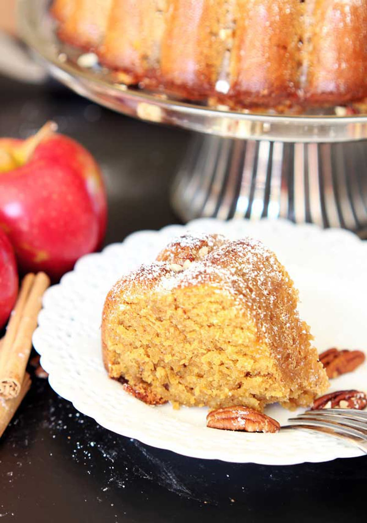 A piece of sliced apple pumpkin bundt cake sitting on a white lace plate, 2 red apples with cinnamon stick and pecans on a black table.