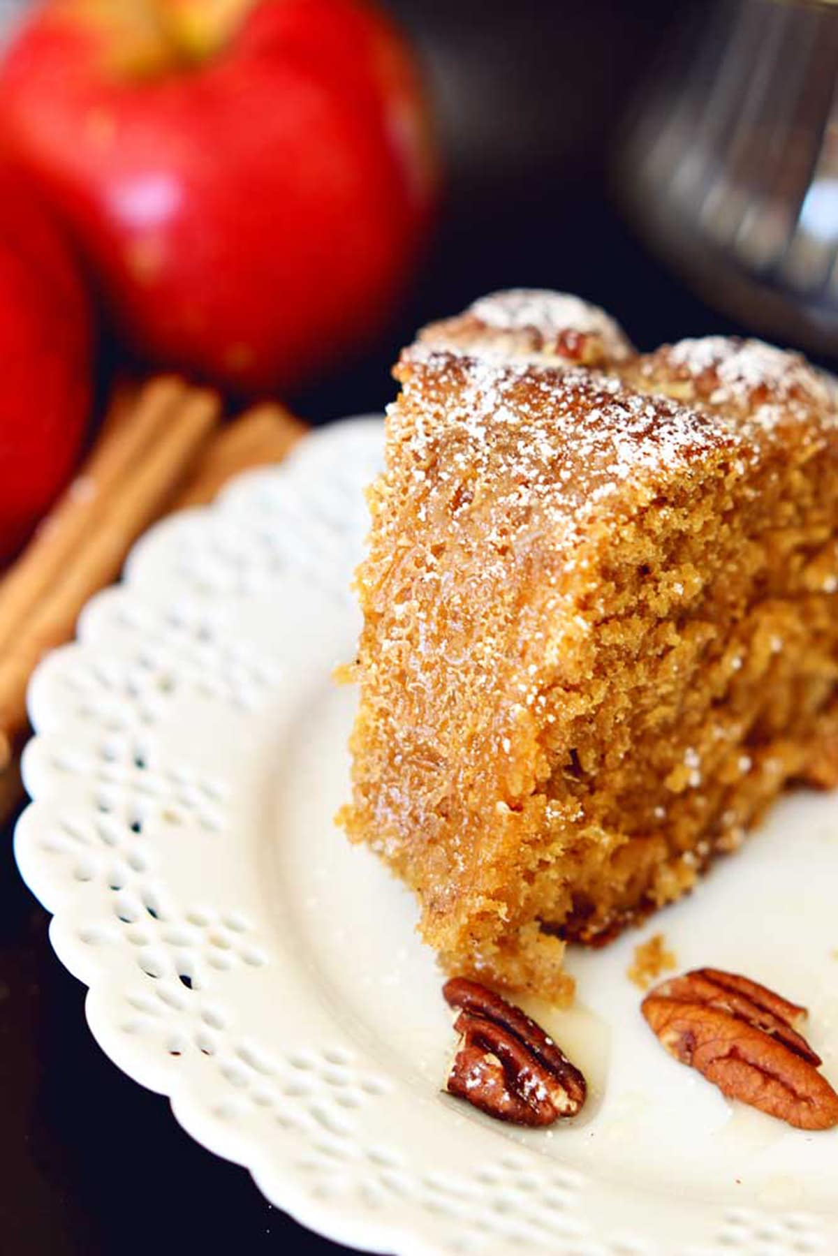 A piece of sliced apple pumpkin bundt cake sitting on a white lace plate, 2 pecans on a plate with apples and cinnamon sticks on black table.
