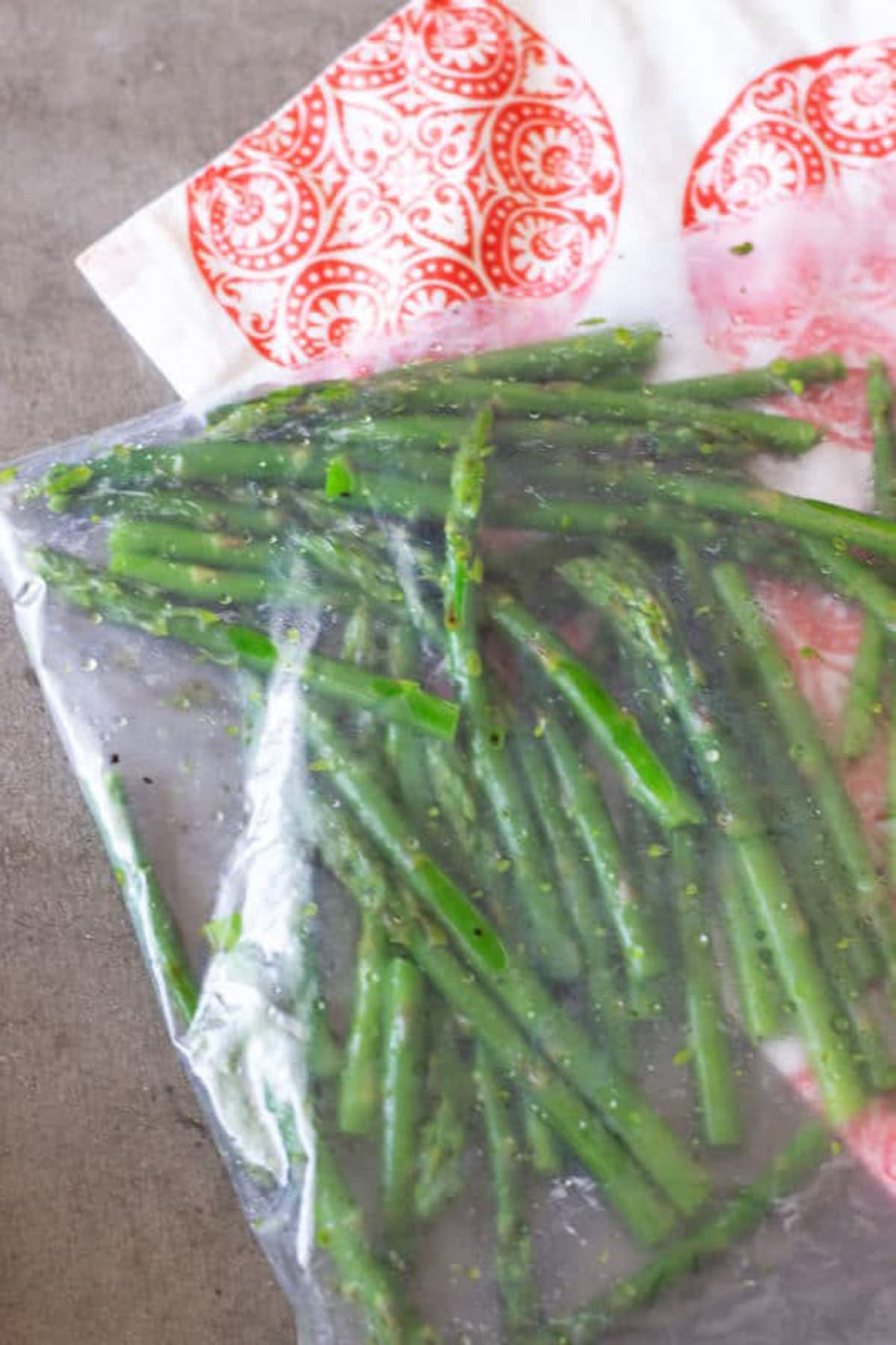Ziplock bag containing asparagus spears with olive oil, salt and pepper.