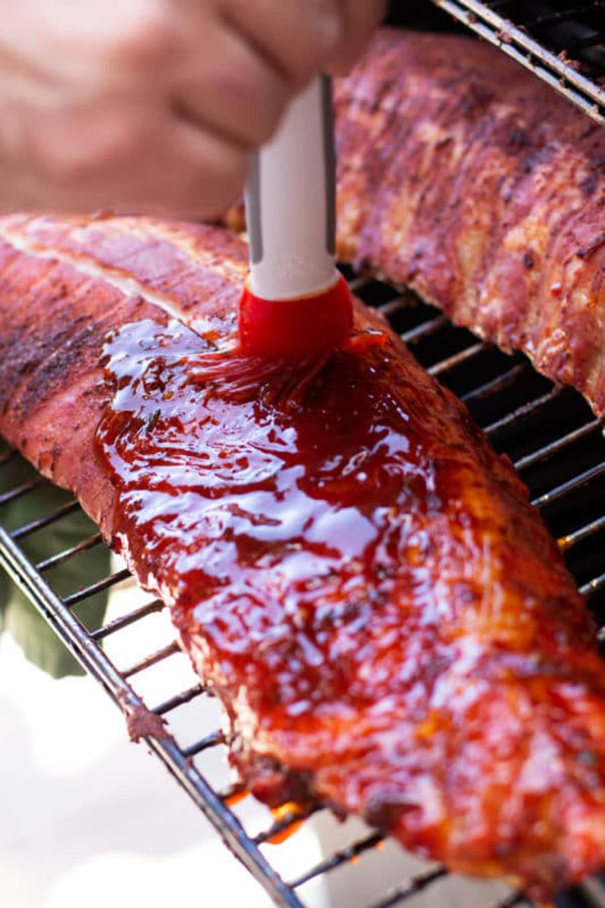 Basting BBQ sauce on a slab of ribs in the smoker.