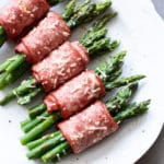 White plate containing asparagus wrapped in bacon topped with Parmesan.