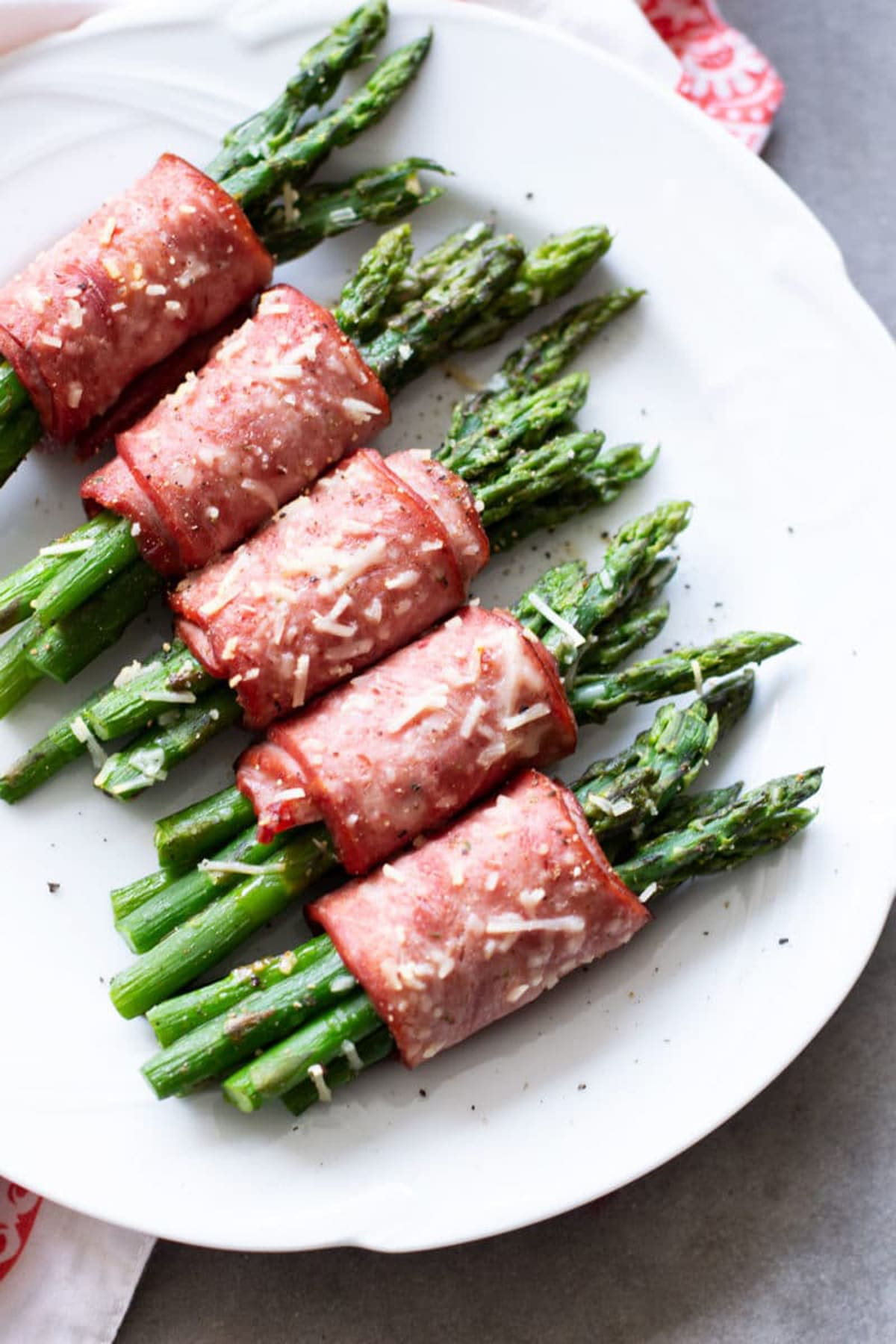 White plate containing five asparagus wrapped in bacon and topped with Parmesan cheese.