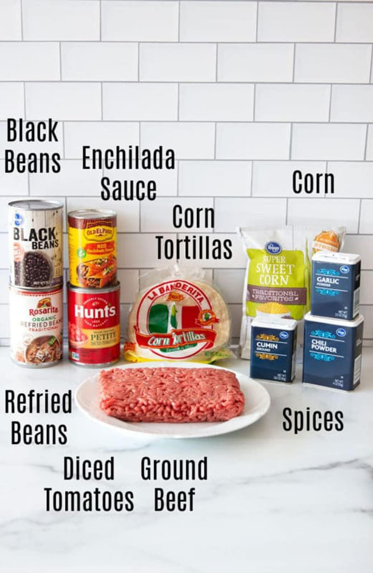 Cans of beans and corn on a counter with spices, tortilla shells, and ground beef.