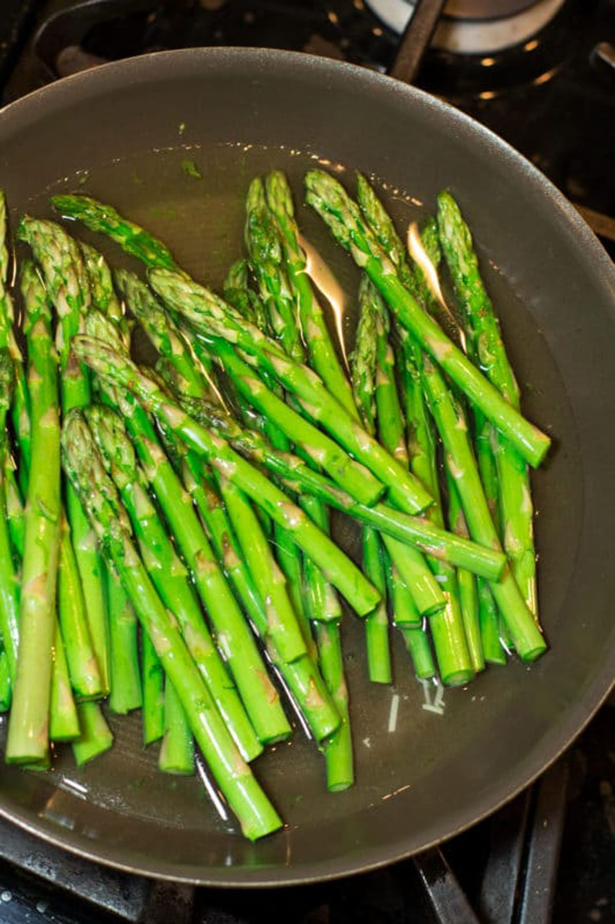 Blanching asparagus spears in a skillet.