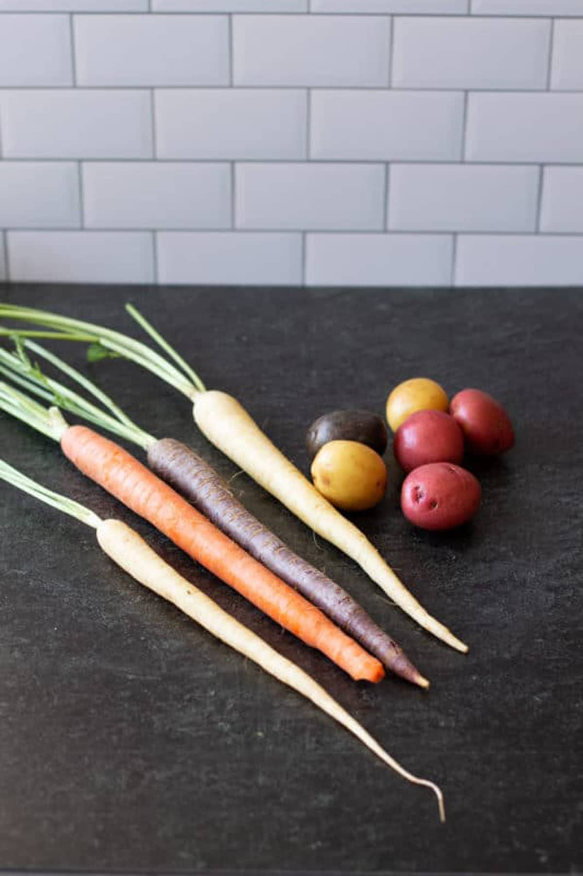 Carrots and new potatoes on black countertop.