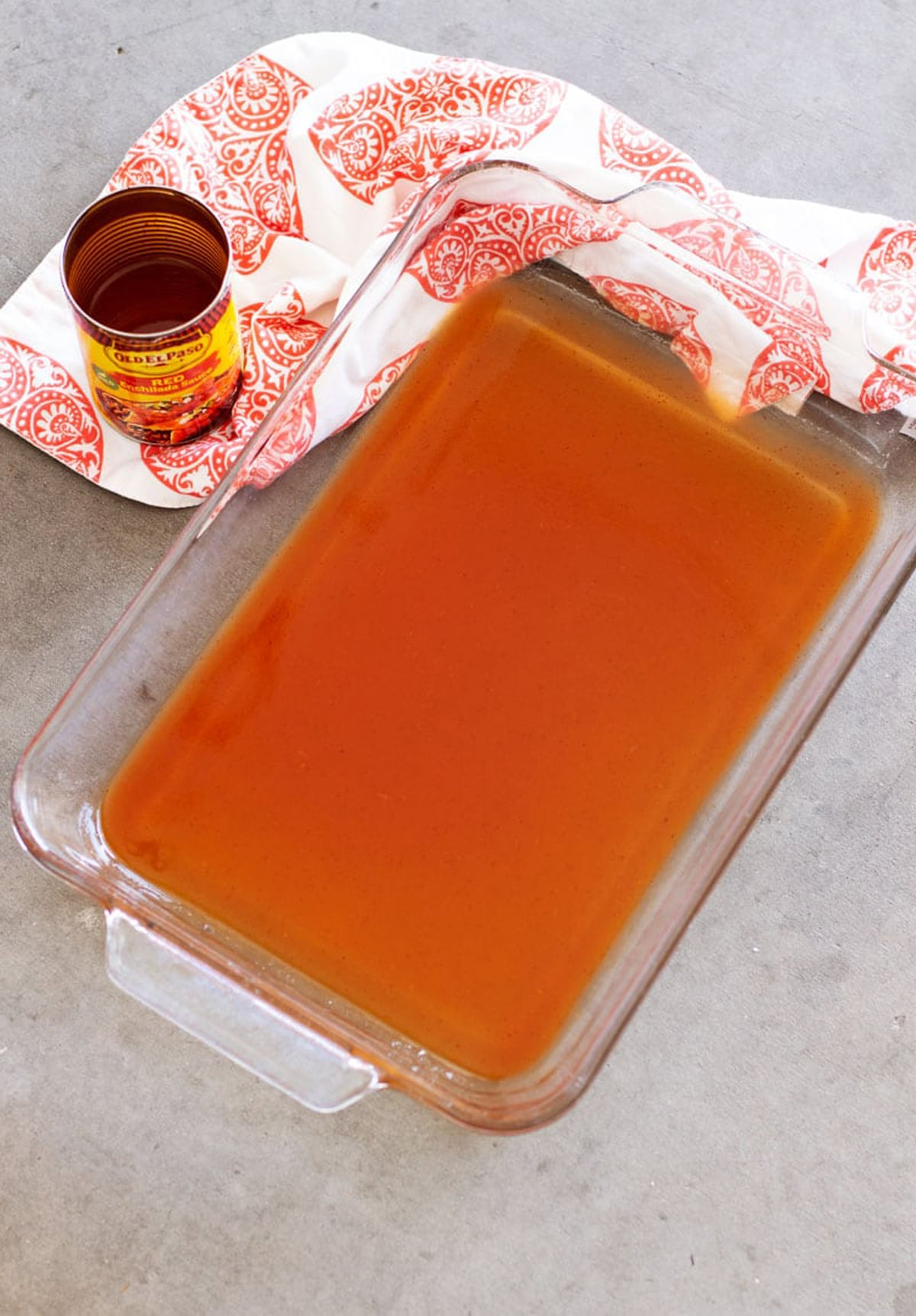 Glass casserole dish containing enchilada sauce.