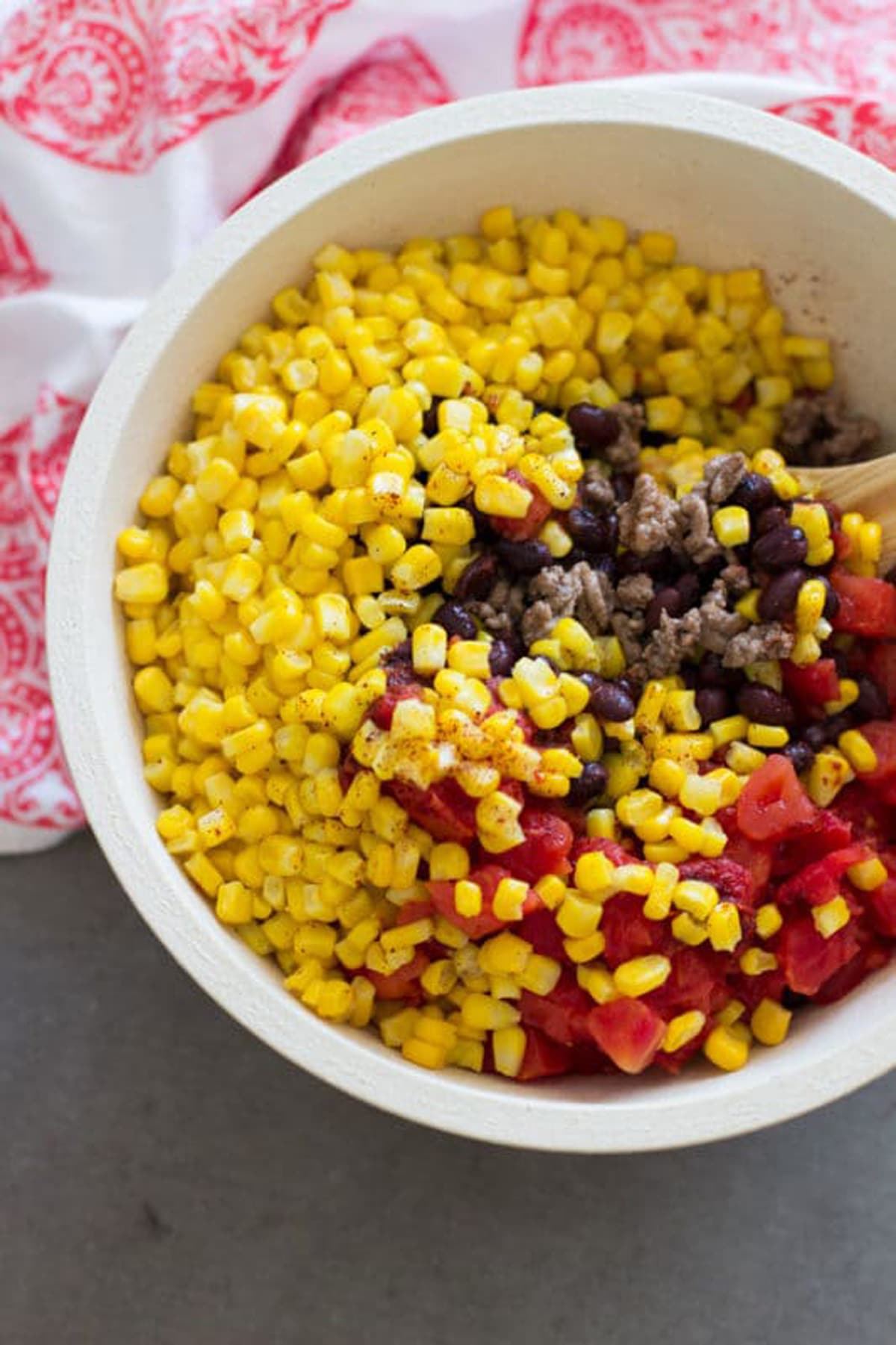 Mixing bowl containing corn, beans,tomatoes, ground beef, and seasoning.