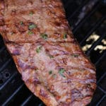 Seared Flank Steak on the grill, topped with fresh parsley.
