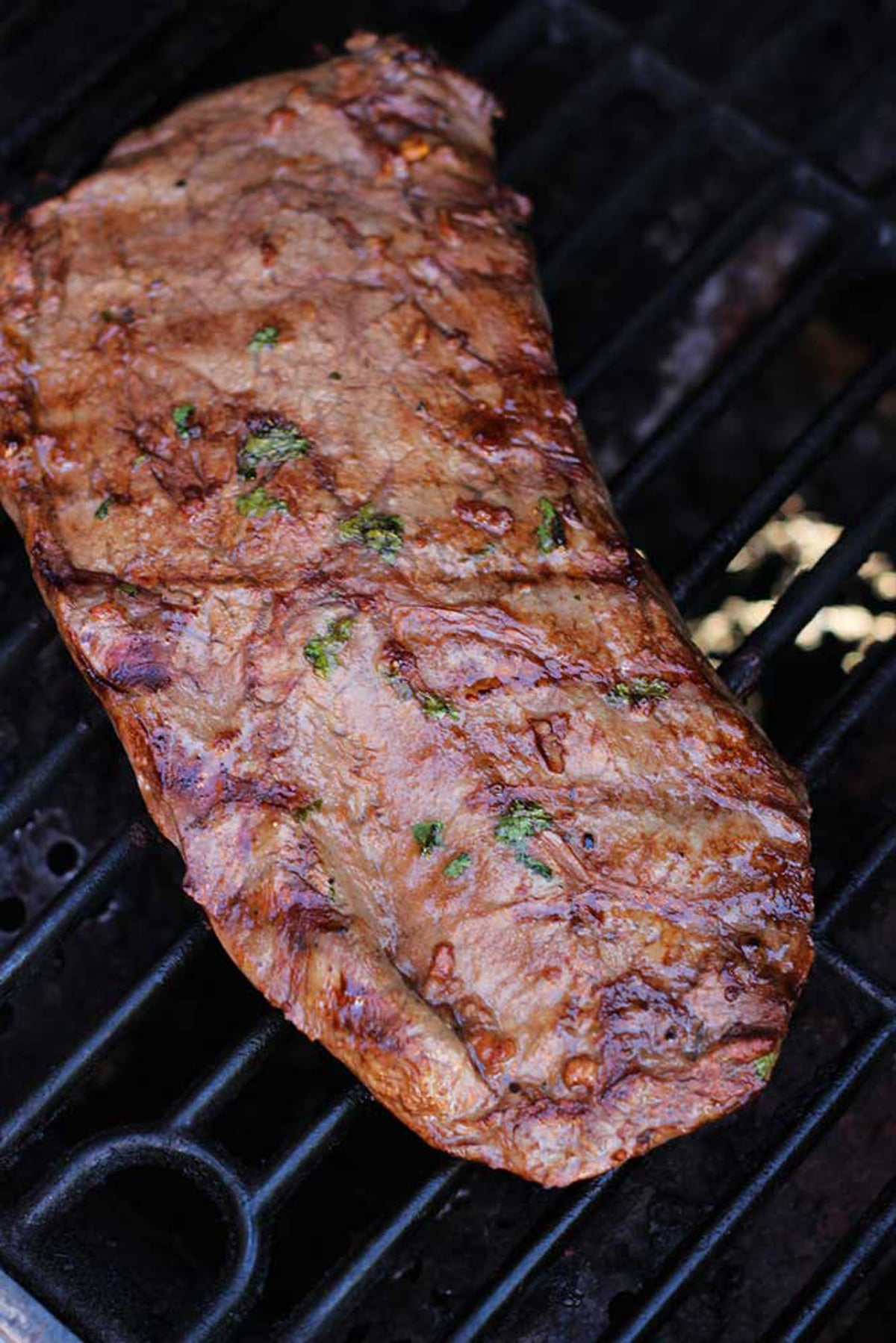 Flank Steak on a grill, seared and topped with fresh parsley.