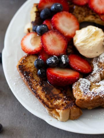 6 slices of french toast sitting on a white plate topped with maple syrup, side of fresh strawberries and blackberries.