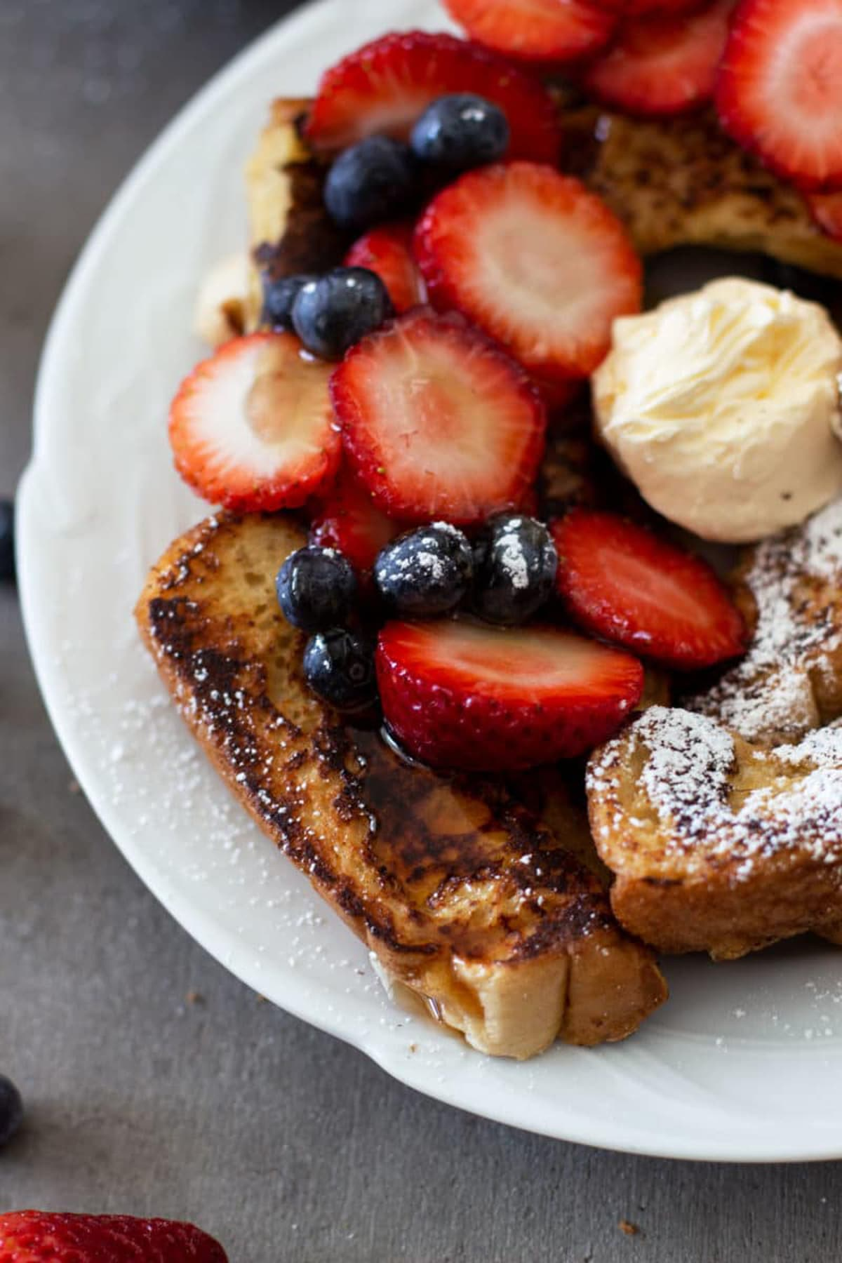 A plate of french toast sticks topped with butter, strawberries, blueberries and powdered sugar.