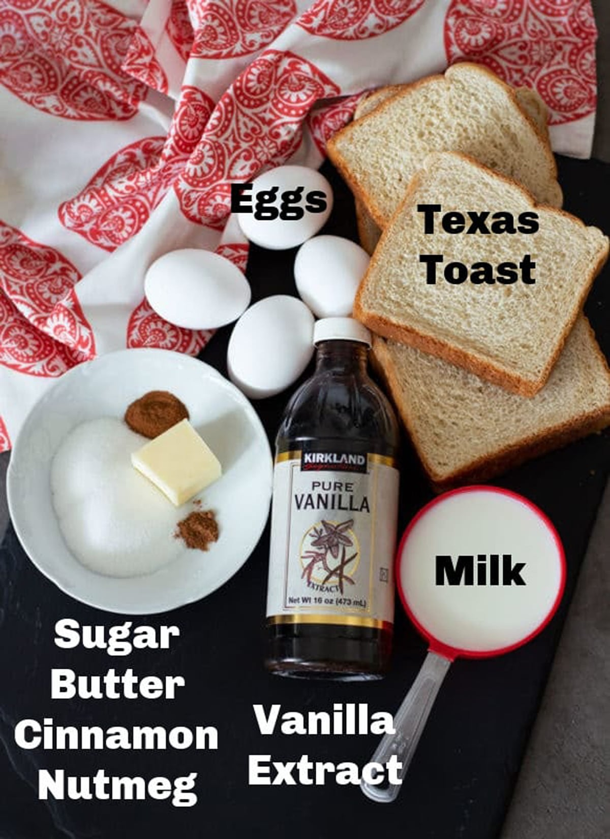 Texas toast, eggs, spices, milk, and vanilla extract on counter.
