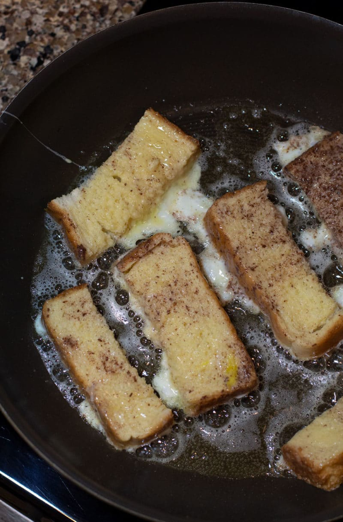 French Toast slices sauteing in butter in a pan.