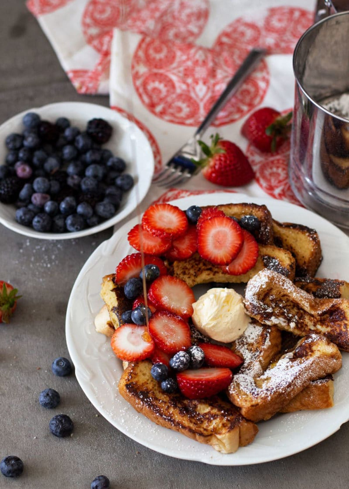 Syrup being poured into a plate of french toast sticks topped with butter, strawberries, blueberries and powdered sugar.