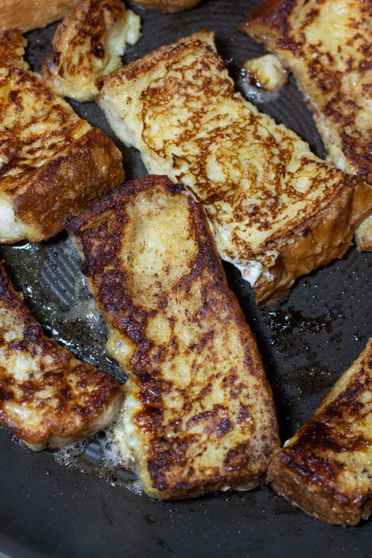 French toast sticks being sauteed in butter in a pan.
