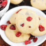 White plate containing 4 Gluten Free Cranberry Cookies, cranberries in bowl on table.