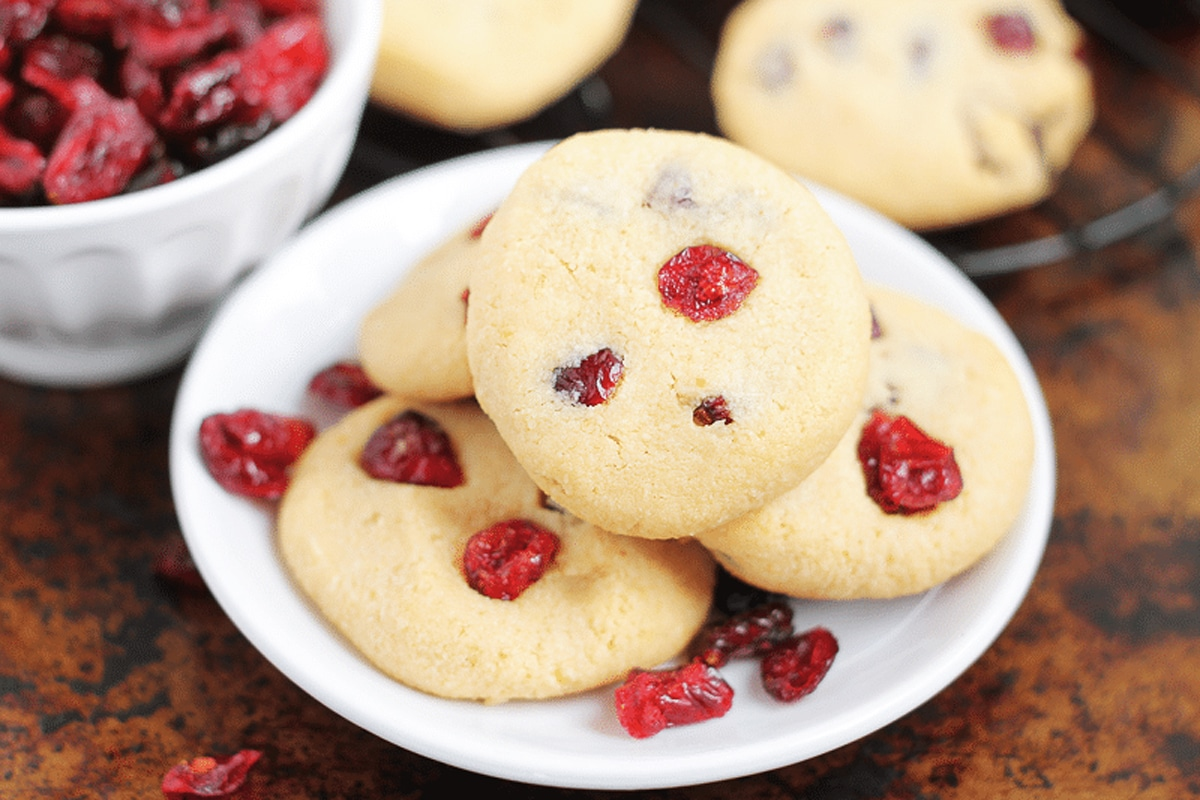 White plate containing 4 cranberry cookies, cookies and cranberries on table.
