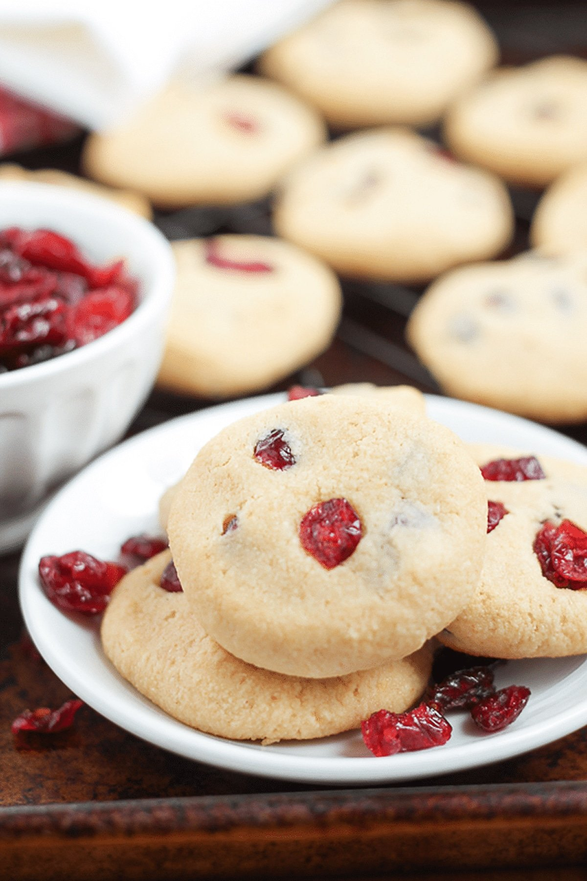 White bowl containing 3 Cranberry Cookies, cranberries and cookies on table.