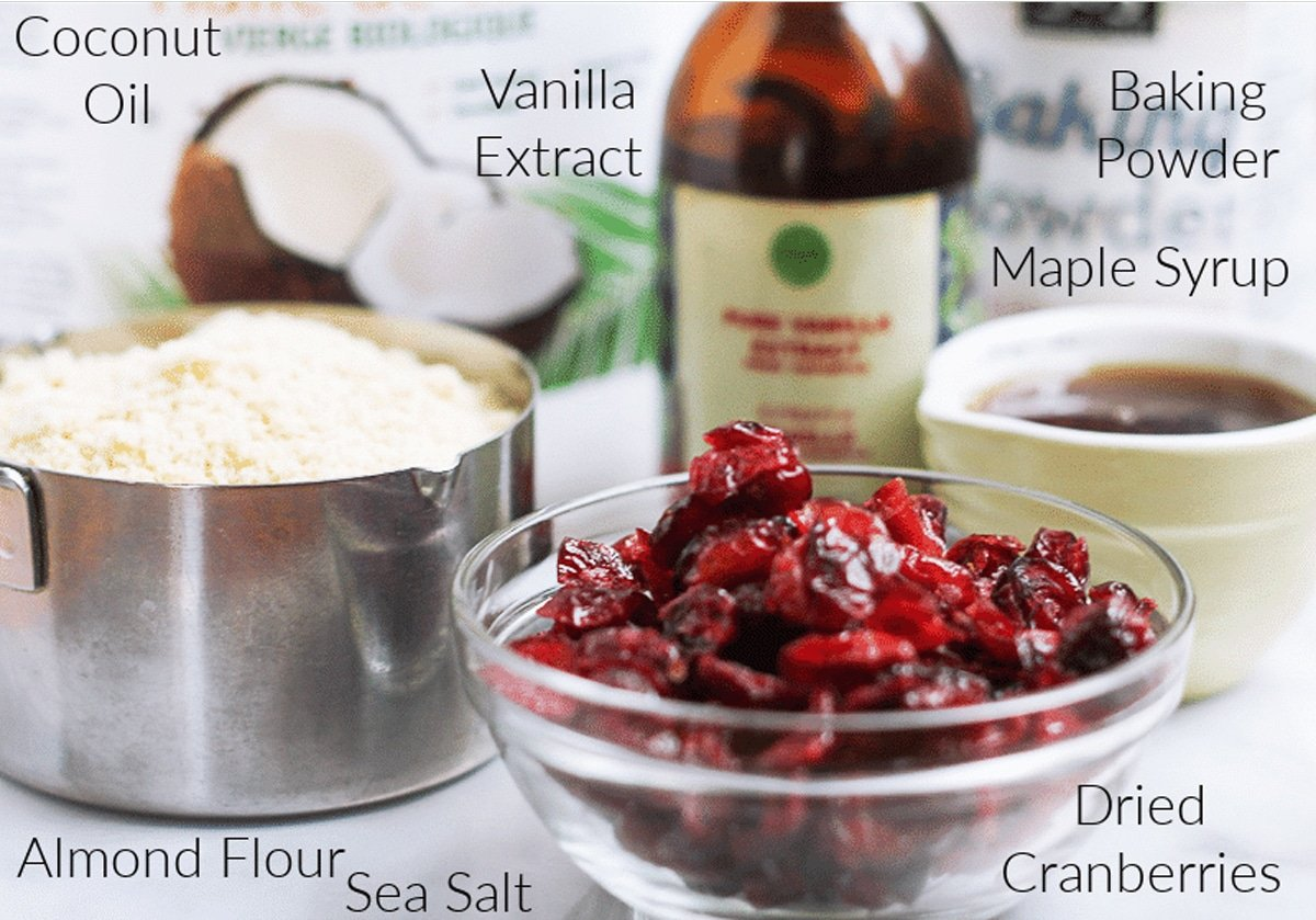 Cranberries, flour, coconut oil, vanilla extract, syrup on a counter to make cookies.