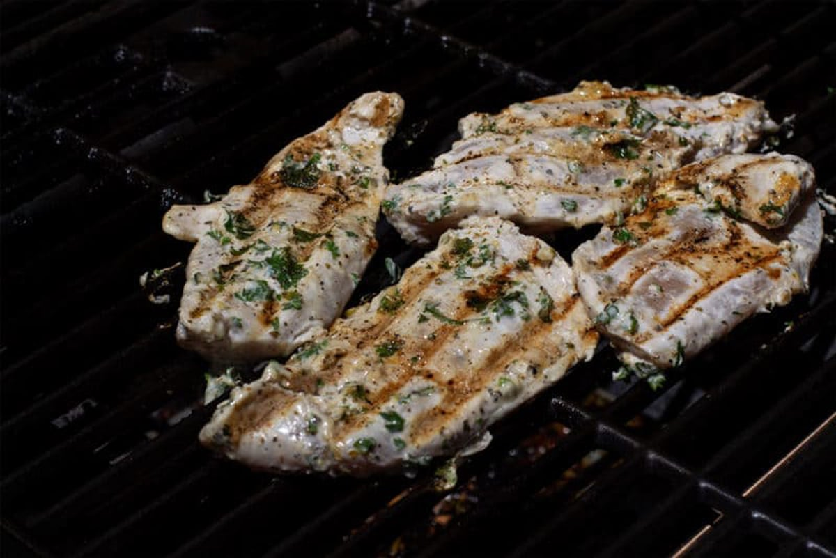 4 pieces of Greek marinated chicken rilling on the grill, grill marks on chicken.
