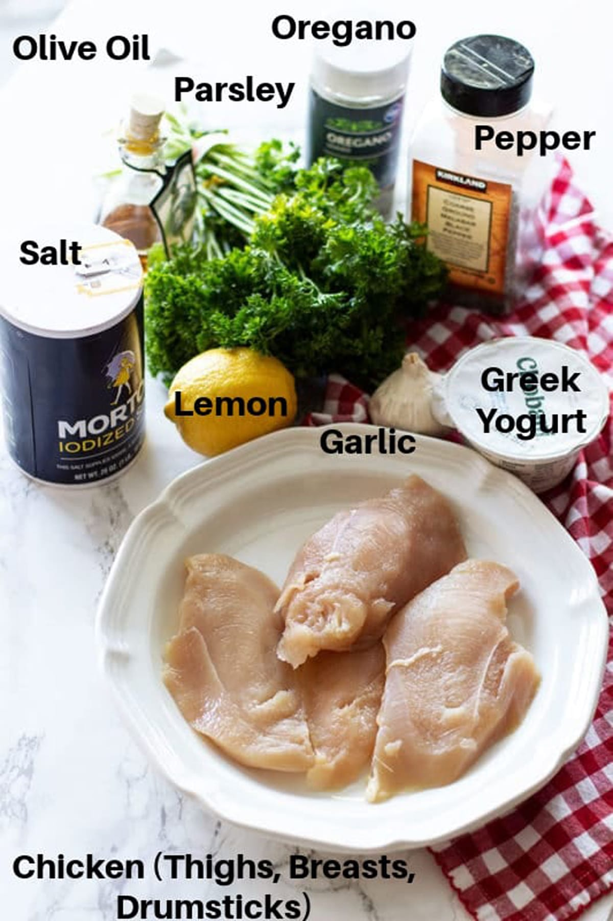 Chicken, lemon, greek yogurt, salt, pepper, oregano and parsley on a table.