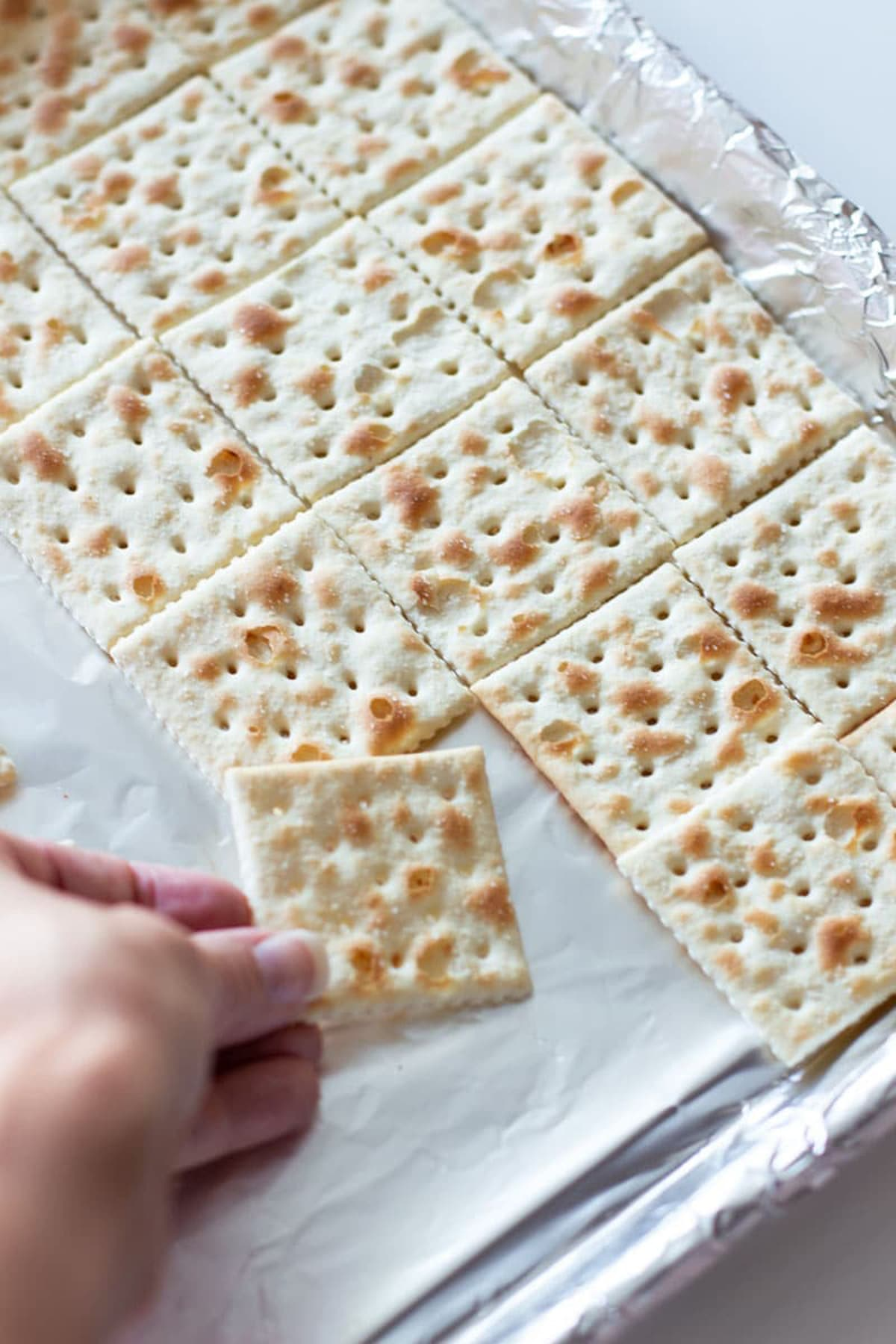 Person's hand placing saltine crackers into a lined cookie sheet for making Halloween Candy Bark.