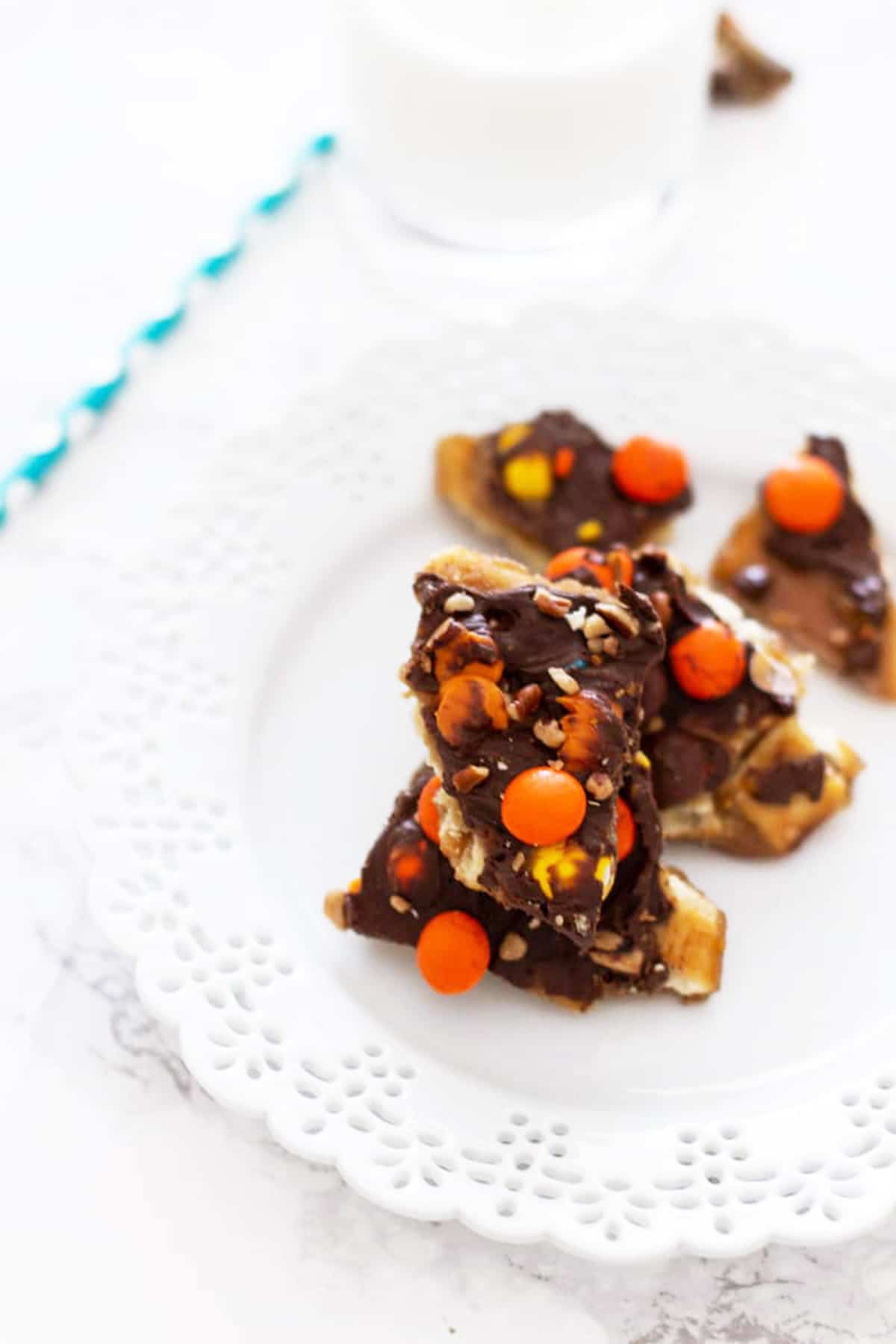 White plate with pieces of Halloween Candy Bark topped with reese's pieces, milk and straw on table.