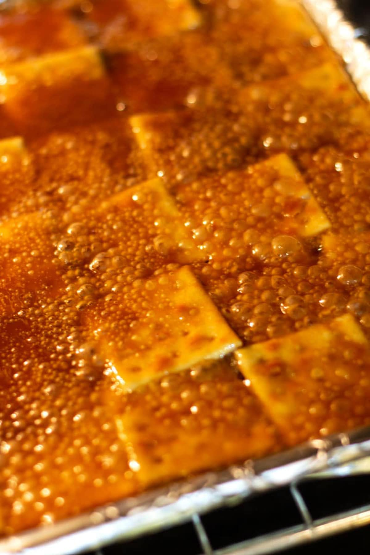 Caramel sauce bubbling in the oven over saltine crackers in preparation for making Halloween bark.