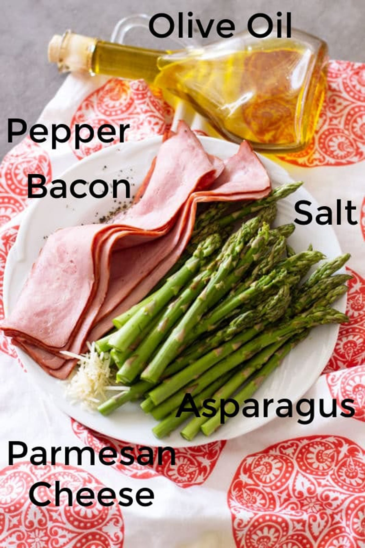 Asparagus, pepper, bacon, salt, olive oil, Parmesan cheese on a counter.