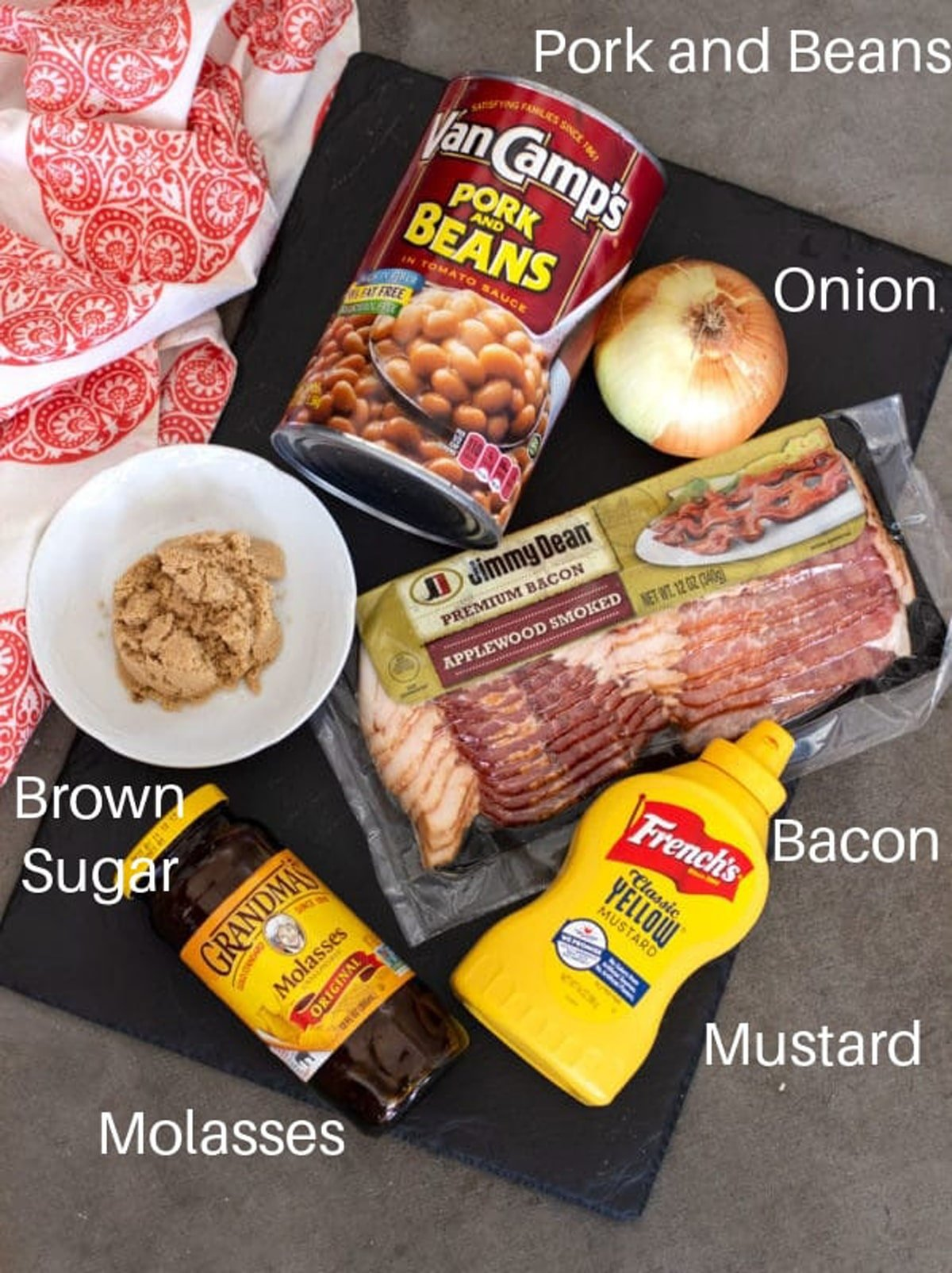 Beans, bacon, onion mustard, and sugar on a counter.