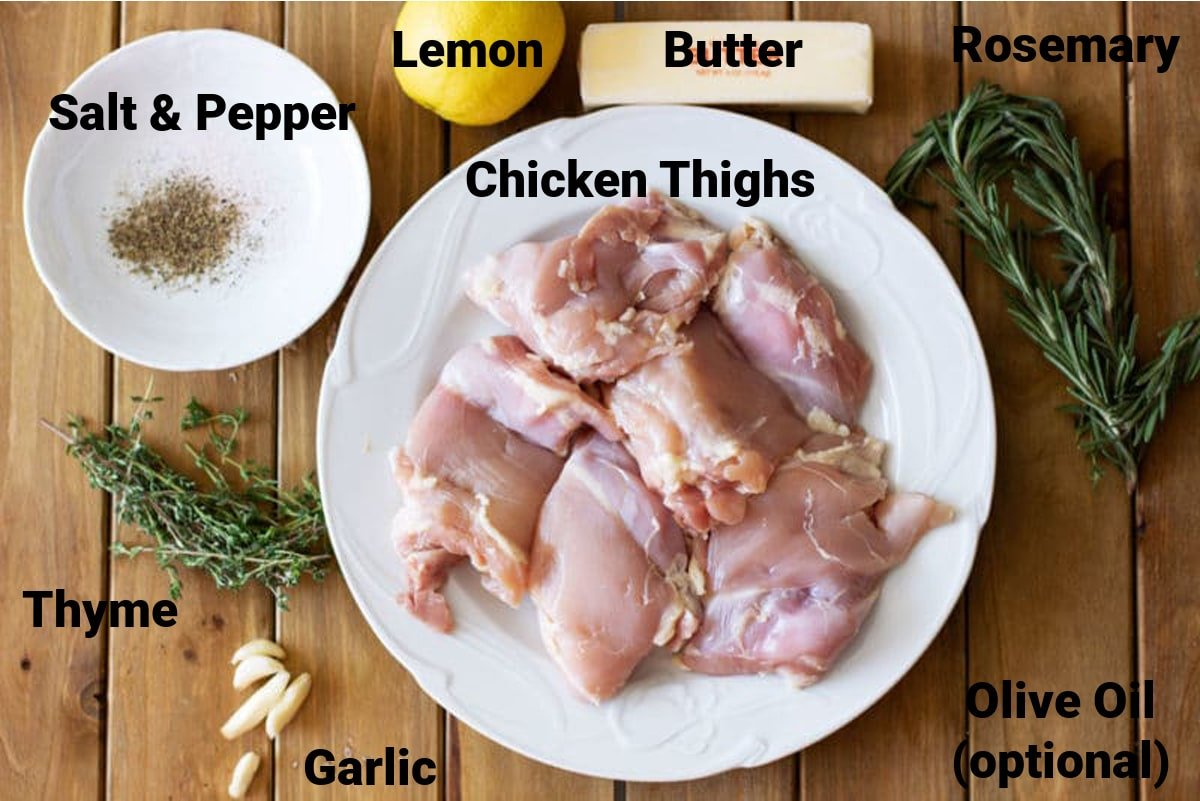 Wooden table containing ingredients for a Lemon Thyme Chicken which includes raw chicken thighs, fresh thyme and rosemary, garlic, butter, lemon, salt and pepper.