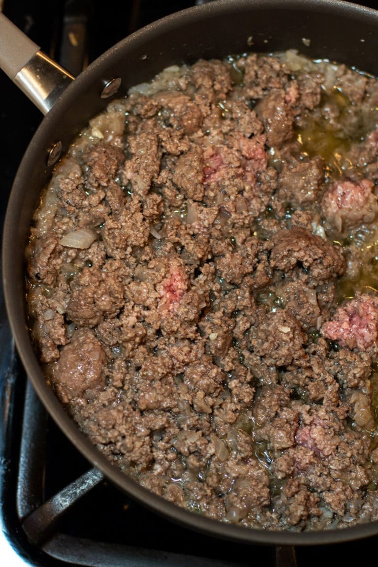 Ground beef and onions browning in a skillet.
