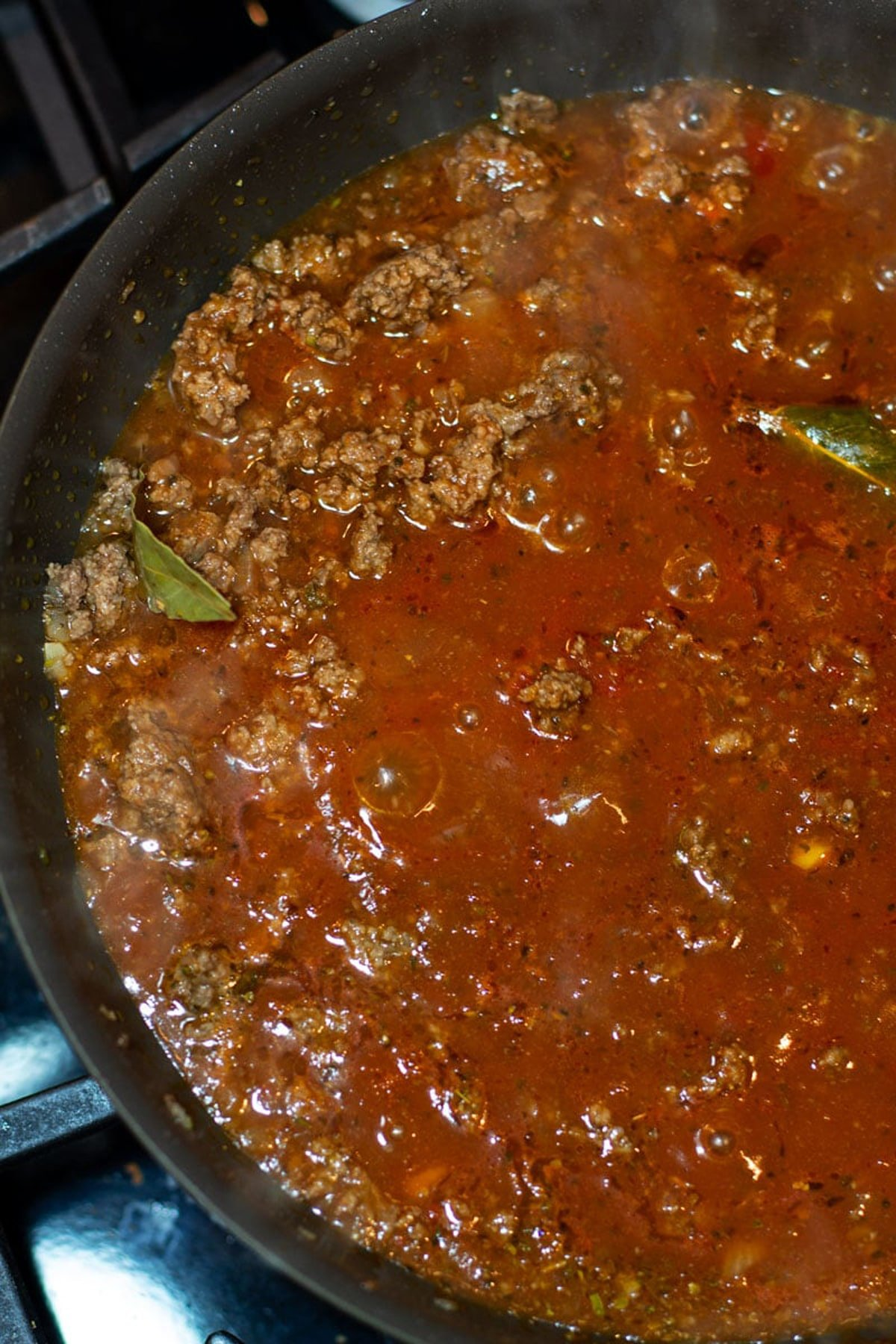 Homemade authentic Italian marinara sauce cooking in a skillet on a stove.