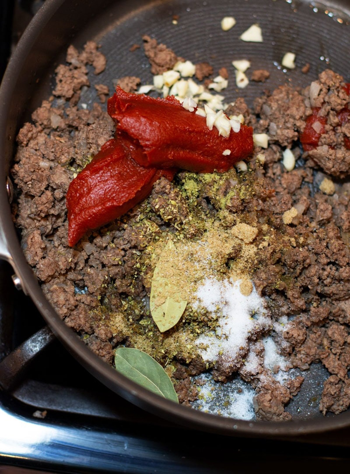 Skillet with Ground beef, tomato paste, and spices in a skillet.